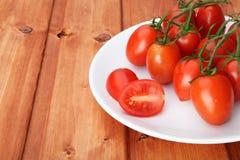 Körsbärsröda tomater på vit pläterar Royaltyfria Bilder