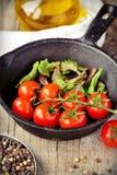Körsbärsröda tomater som lagar mat i panna Arkivbilder