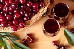 Körsbärsrött vin eller starksprit och mogna saftiga körsbär royaltyfri bild
