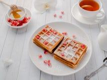 Köstliche appetitliche Wiener Waffeln mit Honig- und Granatapfelsamen auf einer weißen Platte, heller hölzerner Hintergrund Stockfotografie