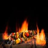 Köstliche Aufsteckspindeln auf Grill mit Feuerflammen Stockfotografie