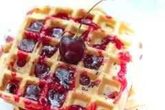 köstliche belgische Waffeln mit Kirschsirup und -Schokoladensplittern auf einer Platte Rote saftige Kirsche an der Spitze lizenzfreie stockbilder