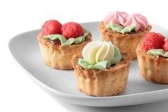 Köstliche bunte kleine Kuchen der Platte lokalisiert auf Weiß Lizenzfreie Stockfotos