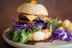 Köstliche Cheeseburgerservierplatte stockfoto