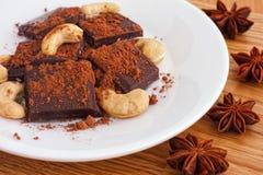 Köstliche defekte dunkle Schokolade mit Kakaopulver- und Acajounüssen und Sternanis lizenzfreie stockbilder