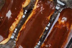 Köstliche Eclairs mit der Schokolade, die auf dem Tisch bereift stockfoto