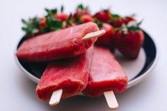 Köstliche Eiscreme haftet mit Erdbeeren auf einem weißen Hintergrund Lizenzfreies Stockbild