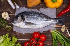 Köstliche frische Fische und Gemüse auf dunklem Weinlesehintergrund Lizenzfreie Stockfotografie