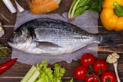 Köstliche frische Fische und Gemüse auf dunklem Weinlesehintergrund Stockbilder