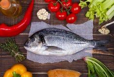 Köstliche frische Fische und Gemüse auf dunklem Weinlesehintergrund Lizenzfreie Stockfotos