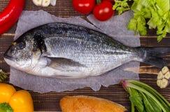 Köstliche frische Fische und Gemüse auf dunklem Weinlesehintergrund Stockbild