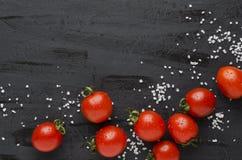 Köstliche frische Tomaten und Salz auf schwarzer Tabelle lizenzfreies stockfoto