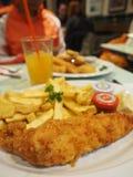 Köstliche gebratene Fisch und mit dem Glas Orangensaft bereit auf einer Platte lizenzfreie stockfotos