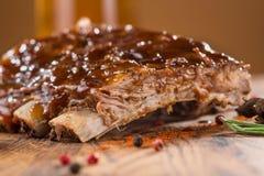 Köstliche gegrillte Rippen würzten mit einer würzigen begießenden Soße und mit gehacktem Frischgemüse auf einem alten rustikalen  stockfoto