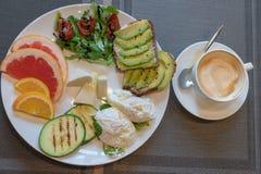 Köstliche gesunde Frühstück Toast mit avacado, getrocknete Tomaten, Käse, apelsin, Pampelmuse, poschiertes Ei, Zucchini auf dem G lizenzfreie stockfotografie