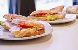 Köstliche heiße Sandwiche mit Truthahn, Geflügelsalat und Tomaten, Schnitt in den Platten auf dem Tisch stockfotografie