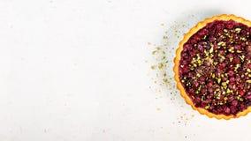 Köstliche homamade Moosbeere, Kirschtörtchen mit Pistazien, Puderzucker auf weißem konkretem Hintergrund für Weihnachten Lizenzfreies Stockbild