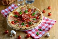 Köstliche italienische Soße der Pizza mit Sahne, Prosciutto, Mozzarella, Kirschtomaten und Basilikum, diente auf einem Holztisch  Stockfotografie