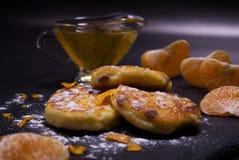Köstliche Käsekuchen mit Rosinen vom selbst gemachten Hüttenkäse Verziert mit Puderzucker und Eifer der Mandarine stockfotografie