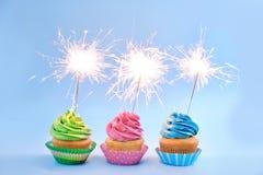 Köstliche kleine Kuchen mit Wunderkerzen Stockfoto