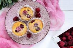 Köstliche Klumpenmuffins mit den frischen Himbeeren, verziert mit Puderzucker Lizenzfreies Stockfoto