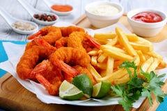 Köstliche knusperige knusprige Parmesankäsebrotkrumen, die Fried Shrimps mit Kalkkeilen, -pommes-Frites und -petersilie beschicht Stockfotos