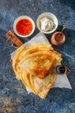 Köstliche Krepps Blinis mit sortierten Soßen auf einem hölzernen Brett Lizenzfreies Stockbild