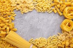 Köstliche Mischteigwaren auf einem grauen konkreten Hintergrund, Rahmen stockbild
