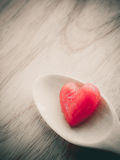 Köstliche nachgemachte Früchte im Herzen formen auf woodedn Tabelle Stockfotografie
