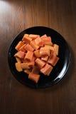 Köstliche Papaya auf dem schwarzen Teller- und Holzhintergrund stockfoto