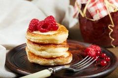 Köstliche Pfannkuchen mit Himbeere und roter Johannisbeere auf Tonwarenplatte Lizenzfreie Stockfotos