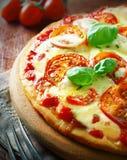 Köstliche Pizza mit goldenem gegrilltem Käse Lizenzfreies Stockbild