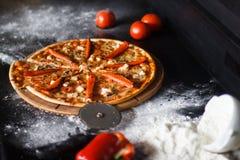 Köstliche Pizza mit Käse und Gemüse auf schwarzem Hintergrund Stockfoto