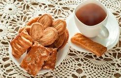 Köstliche Plätzchen und Keks der Vielzahl mit Schale heißem Tee stockfotos