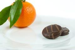 Köstliche Pralinen beschichteten in der glatten dunklen Schokolade auf Platte Lizenzfreie Stockbilder