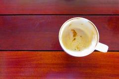 Köstliche Schale bis vollständig leere Kaffeetasse auf hölzerner Tabelle Lizenzfreie Stockbilder
