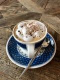 Köstliche Schale Cappuccino bedeckt mit Schokoladenpulver Stockbilder
