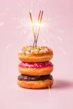 Köstliche Schaumgummiringe für Geburtstag auf Pastellrosahintergrund lizenzfreie stockfotos