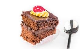 Köstliche Scheibe des Schokoladenkuchens mit Sahne und der Zuckersüßigkeit auf Oberseite nahe einem Löffel Lizenzfreies Stockbild