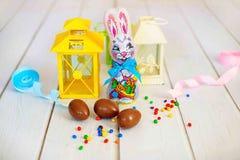 Köstliche SchokoladenOstereier und Bonbons und Kaninchen auf hölzernem Hintergrund Stockbild