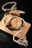 Köstliche Schokoladenplätzchen in einem Teller auf dem hölzernen schwarzen Hintergrund verziert mit einem Seil Lizenzfreies Stockfoto