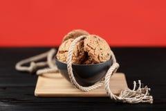 Köstliche Schokoladenplätzchen in einem Teller auf dem hölzernen schwarzen und roten Hintergrund verziert mit einem Seil Stockfoto
