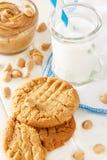 Köstliche selbst gemachte Erdnussbutterplätzchen mit Becher Milch Weißer hölzerner Hintergrund Gesunder Snack oder geschmackvolle Stockfoto