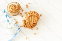 Köstliche selbst gemachte Erdnussbutterplätzchen mit Becher Milch Weißer hölzerner Hintergrund Gesunder Snack oder geschmackvolle Lizenzfreies Stockbild