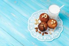 Köstliche selbst gemachte Schokoladenmuffins und Glas Milch mit sortierten Nüssen Lizenzfreies Stockbild
