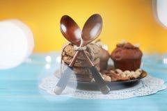 Köstliche selbst gemachte Schokoladenmuffins und -kekse auf gelbem und blauem Weinlesehintergrund Stockbild