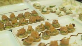 Köstliche Snäcke und Canape auf Tabelle an der Ereignispartei Schließen Sie herauf appetitanregende Snäcke auf Parteitabelle am F stock video footage