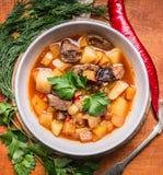 Köstliche Suppe mit Lamm und Kartoffeln mit Kräutern in der weißen Platte auf einem hölzernen Hintergrundabschluß des Schneidebre stockfotos