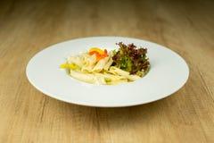 Köstliche Teigwaren auf Platte auf Holztisch Stockfotos