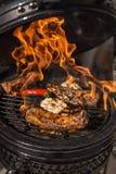 Köstliche würzige marinierte Schweinsrippchen auf heißem loderndem Grill grill Restaurant Lizenzfreie Stockbilder